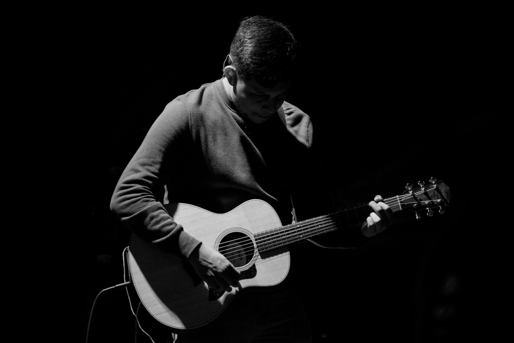 Man playing small size guitar