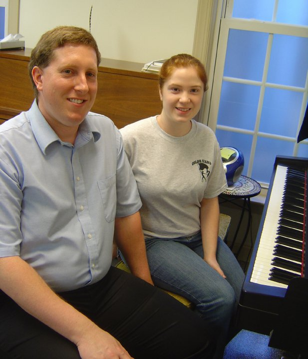 Jamie teaching a student the piano