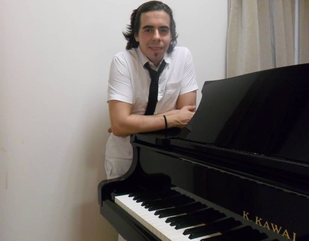 Pablo standing next to piano